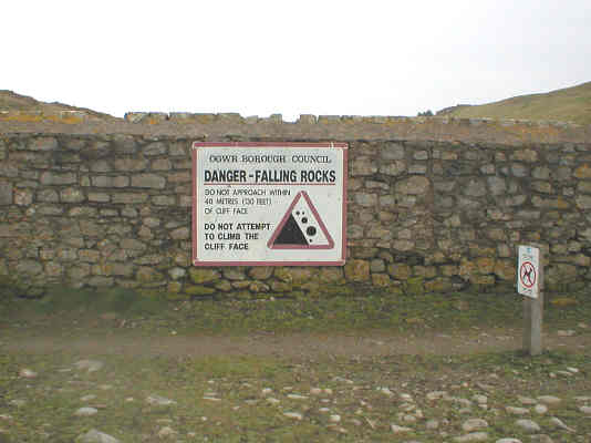 Signage warning not to attempt to climb the cliff face owing to the danger of falling rocks